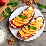 Lätt råg skjuter in med mjuk ost, nya nektarinskivor och valnötter Smakliga sommarsmörgåsar på en platta Arkivfoton