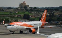 Lätt stråle för low costtrafikflygplan som parkeras på Malta den internationella flygplatsen arkivbild
