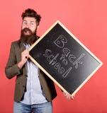 lätt take Läraren uppsökte mannen rymmer svart tavla med inskriften tillbaka till röd bakgrund för skolan Lärare med ovårdat royaltyfri bild