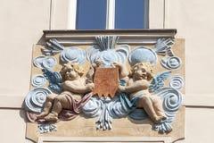 Lättnad på fasad av gammal byggnad, två kupidon i blåa dekorativa motiv, Prague, Tjeckien fotografering för bildbyråer