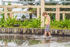 Läufe des kleinen Jungen durch eine Pfütze Sommer im Freien lizenzfreie stockbilder