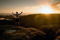 Läufer auf der Spitze Mann in seinem Zielgestentriumph mit den Händen in der Luft Verrückter Mann in den schwarzen Hosen und im w Lizenzfreies Stockbild