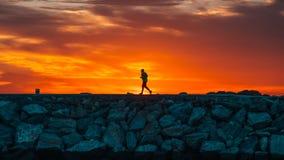 Läufer bei Sonnenaufgang mit der Sonne, die das Schattenbild herstellt stockbild