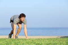 Läufer bereit, auf dem Gras zu laufen Lizenzfreie Stockbilder