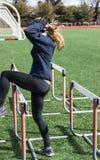 Läufer, der über Hürden für Stärke, Balance und Beweglichkeit steping ist lizenzfreies stockfoto