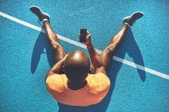 Läufer, der auf einer Bahn überprüft seine Rundenzeit sitzt lizenzfreie stockfotos