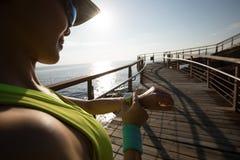 Läufer, der die Sportuhr vor Lauf auf Sonnenaufgangküste gründet Lizenzfreie Stockfotografie
