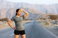 Läufer, der eine Pause auf einer Wüstenstraße macht stockfotos