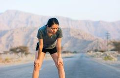 Läufer, der eine Pause auf einer Wüstenstraße macht lizenzfreie stockbilder