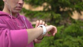 Läufer, der intelligenten Uhrtimer und -betrieb beginnt Mann, der Herzfrequenzmonitor bevor dem Rütteln überprüft stock footage