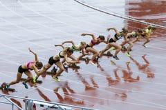 Läufer der jungen Frau, die das Rennen beginnen Stockbilder