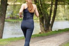Läufer der jungen Frau, der morgens im Park rüttelt Stockbilder
