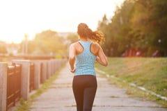 Läufer der jungen Frau, der morgens im Park rüttelt Lizenzfreies Stockbild