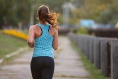 Läufer der jungen Frau, der morgens im Park rüttelt Lizenzfreie Stockbilder