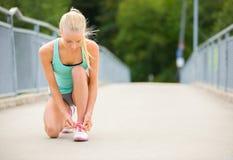 Läufer der jungen Frau, der Spitzee auf Brücke bindet Stockfoto