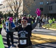 Läufer, der an der Kamera während eines Danksagungswochenendenrennens wellenartig bewegt stockfotos