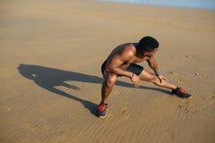 Läufer, der Kniesehne für das Aufwärmen bevor dem Laufen ausdehnt Lizenzfreies Stockfoto