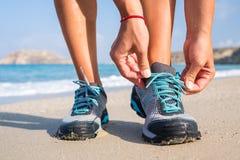 Läufer, der Spitzee auf dem Strand bindet Stockfotografie