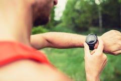 Läufer, der Sportuhr überprüfend schaut Lizenzfreie Stockfotos