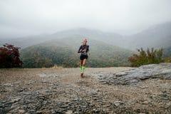 Läufer des jungen Mädchens, der in Regen mit einem Lächeln auf Gesicht läuft lizenzfreie stockfotografie
