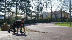 Läufer des jungen Mannes an Anfangszeile in Blockanfangsposition auf Rennstrecketraining in einem Park stock video footage