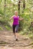 Läufer des recht jungen Mädchens im Wald Stockfoto