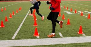 Läufer, die über orange Kegeln ausbilden lizenzfreies stockbild