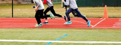 Läufer, die auf einer roten Bahn in der Kälte ausbilden lizenzfreie stockfotos