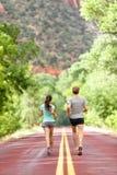 Läufer, die auf Straße in der Natur weg von Kamera laufen Lizenzfreie Stockfotografie