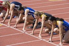 Läufer, die für Rennen an den Startblöcken sich vorbereiten lizenzfreie stockbilder