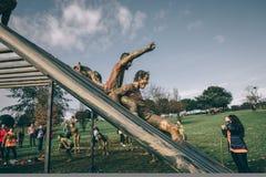 Läufer, die Struktur in einem Test des extremen Hindernisrennens hinuntergehen Lizenzfreie Stockfotografie