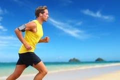 Läufer hörende Smartphonemusik, die auf Strand läuft Stockbild