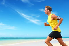 Läufer laufende hörende Smartphonemusik auf Strand Stockfotos