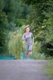 Läuferathlet, der auf Parkspur läuft rüttelnde Arbeit der Fraueneignung Stockfotografie