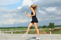 Läuferathlet, der auf Straße läuft Wellnesskonzept Training des Fraueneignungssonnenaufgangs rüttelndes Lizenzfreie Stockfotos