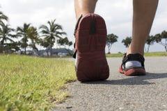 Läuferfüße, die auf Straße am Park laufen Stockbilder