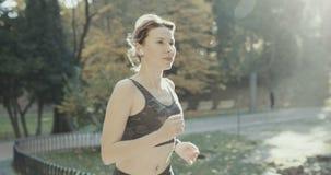 Läuferfrau, die in den Park draußen ausübt tragbare Technologie des Eignungsverfolgers läuft stockbilder