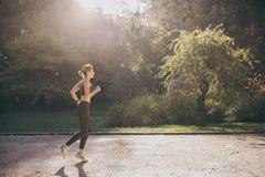 Läuferfrau, die in den Park draußen ausübt tragbare Technologie des Eignungsverfolgers läuft stockfoto