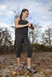 Läuferfrau, die Zeit- und Pulsschlag überprüft Stockbilder