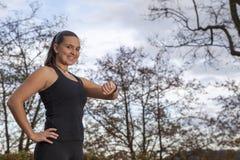 Läuferfrau, die Zeit- und Pulsschlag überprüft Lizenzfreie Stockfotos