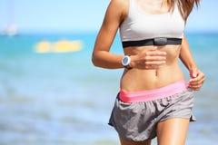 Läuferfrau mit Herzfrequenzmonitorbetrieb Stockfoto