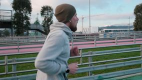 Läufermann bildet auf Stadion aus und schaut auf seinem smartwatch in der Tageszeit stock footage
