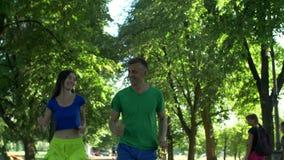 Läufermann, der mit Frau während des Rüttelns flirtet stock footage