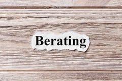 Läxa upp av ordet på papper Begrepp Ord av att läxa upp på en träbakgrund arkivbild