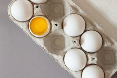 Låda av rå fega ägg på grå bakgrund broken ägg yolk fotografering för bildbyråer