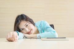 Låg den asiatiska kvinnan för closeupen på skrivbordet med den lyckliga framsidan i vilotid fr Royaltyfria Bilder