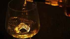 Låg ljus längd i fot räknat av bourbon, konjak eller whisky som hälls i vinexponeringsglas på den mörka tabellen arkivfilmer