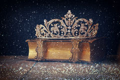 Låg nyckel- bild av den dekorativa kronan på den gamla boken Filtrerad tappning royaltyfri bild