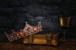 låg nyckel- bild av den härliga drottning-/konungkronan på den gamla boken royaltyfria bilder