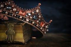 låg nyckel- bild av den härliga drottning-/konungkronan på den gamla boken royaltyfria foton